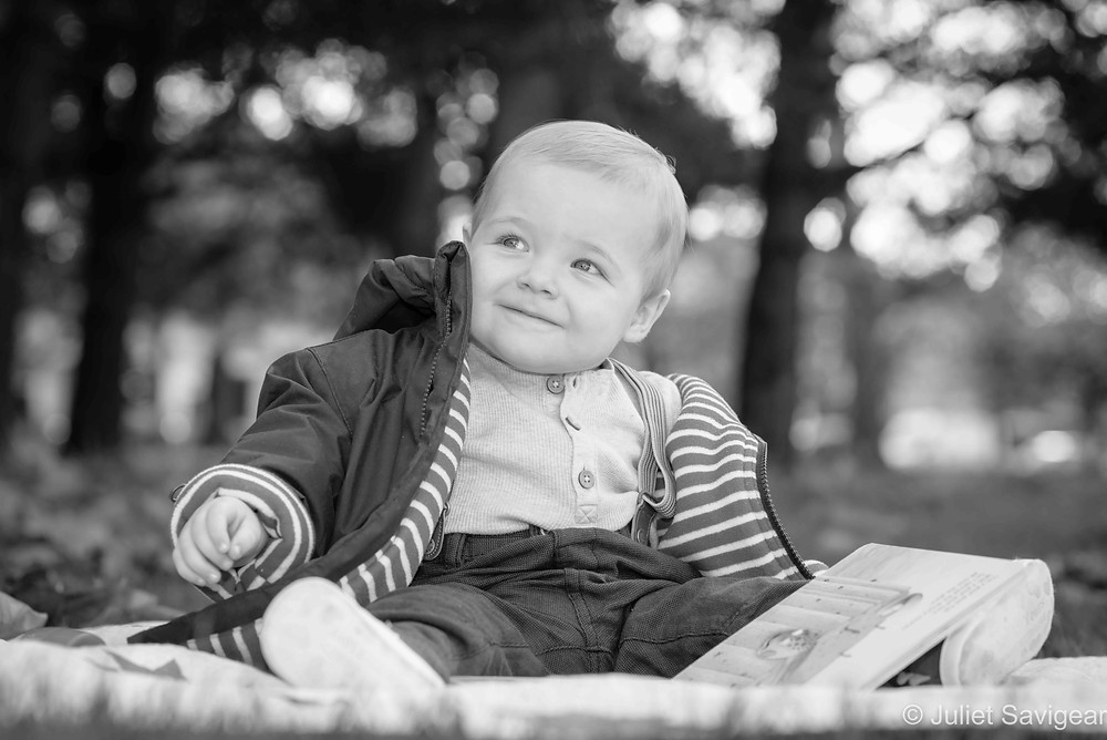 Baby boy reading his book in the park