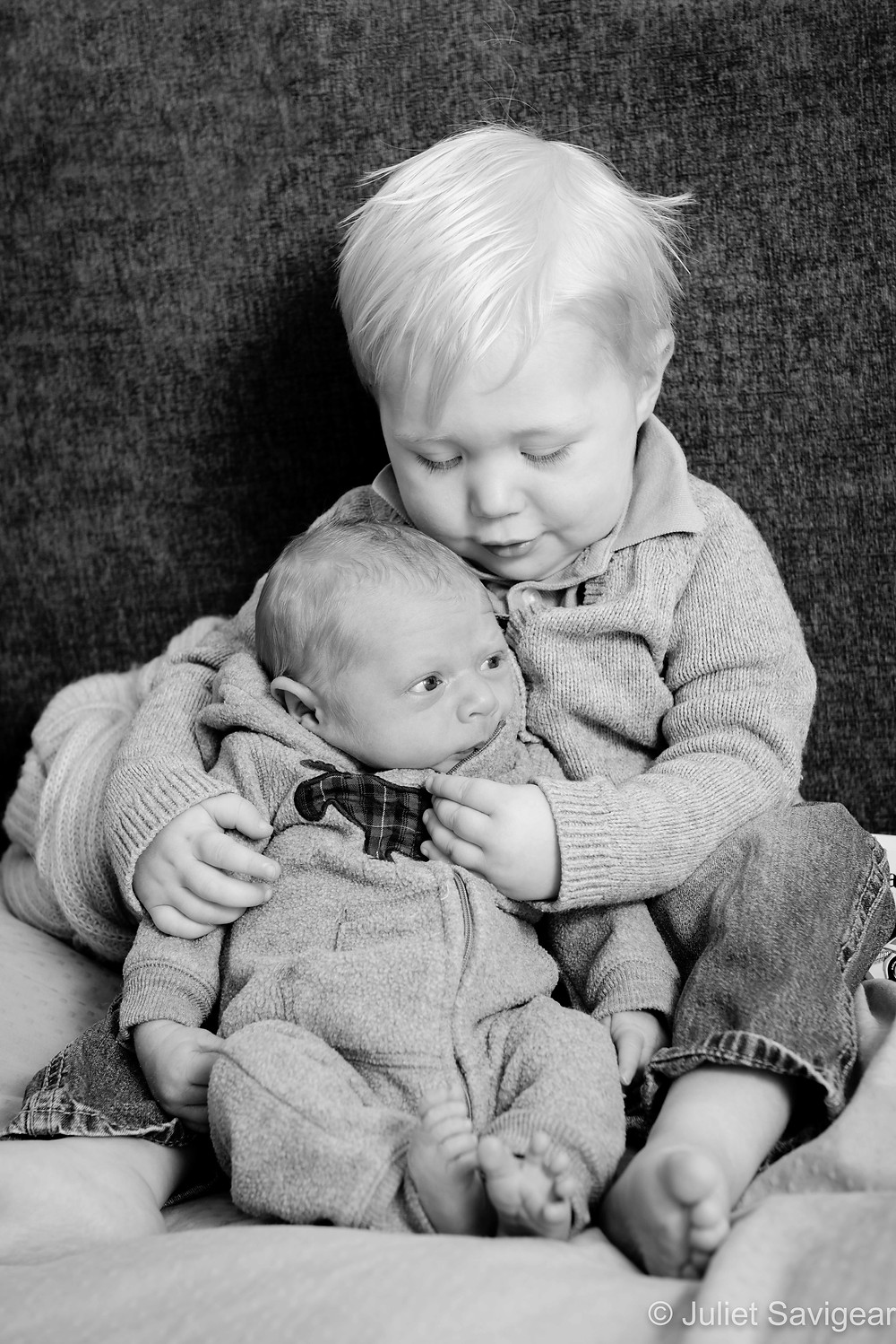 Toddler cuddling baby brother
