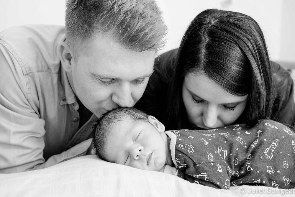 Mummy and daddy kissing newborn baby