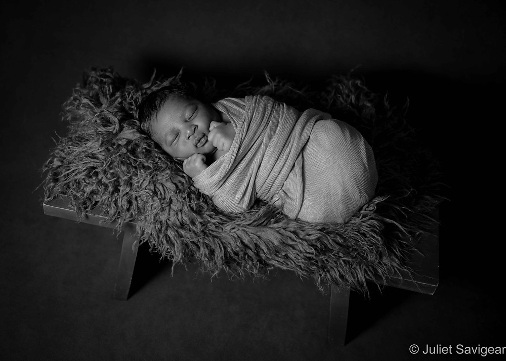 Newborn baby sleeping on bench