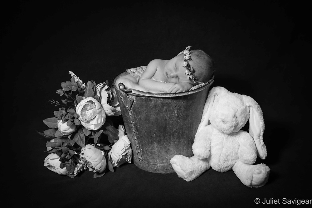 Newborn baby with flowers and toy rabbit