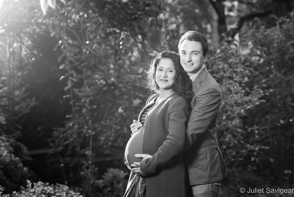 Expectant couple in enchanted garden