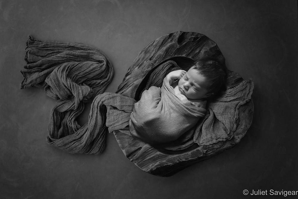 Newborn baby in wooden bowl