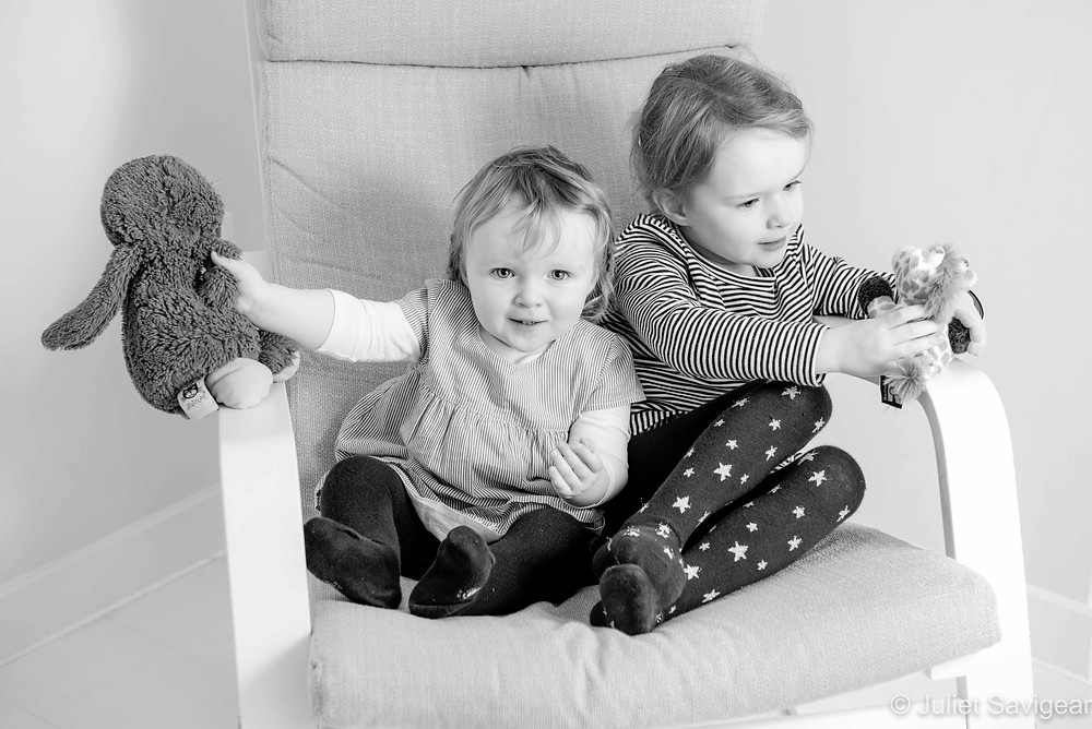 Sisters on a chair with their soft toys
