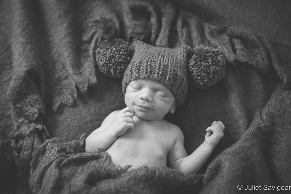 Newborn baby in pom pom hat
