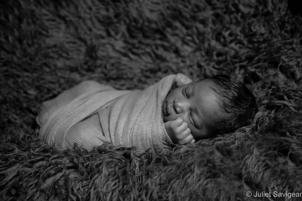 Baby boy snuggled on fur