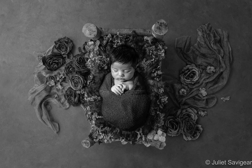 Baby in cot bed with flowers