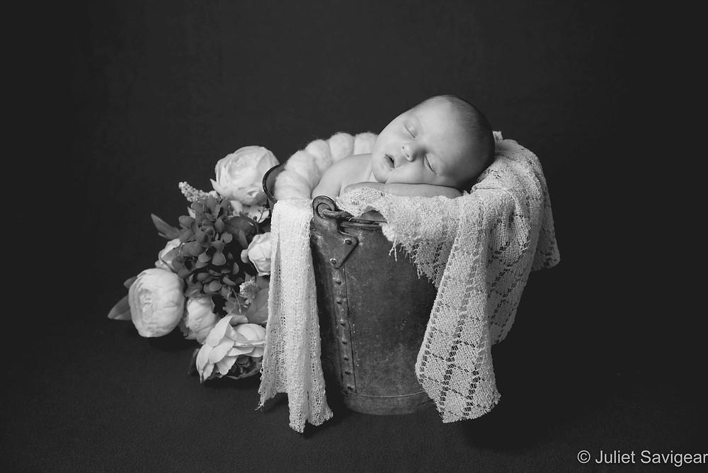 Newborn baby sleeping in a bucket
