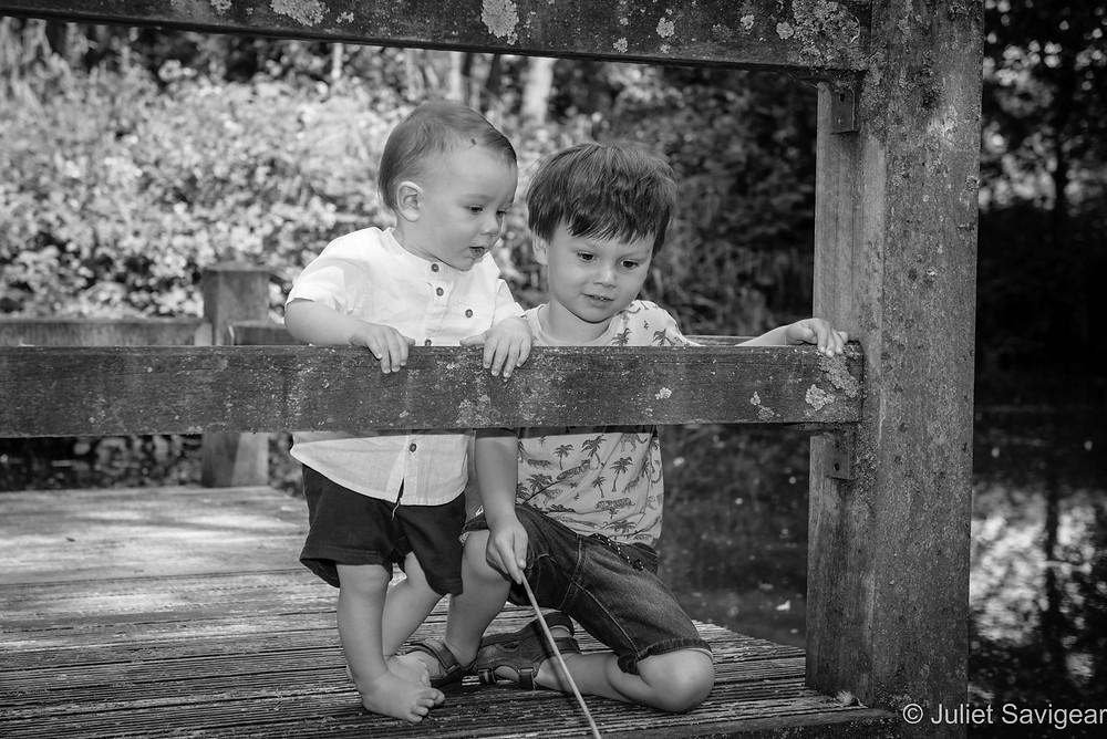 Children pretending to fish in pond