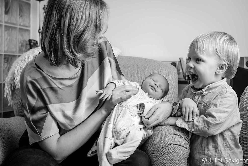 Excited toddler with newborn baby