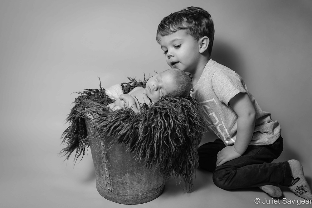 Toddler with baby brother in a bucket