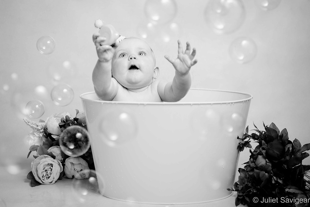 Baby in bath tub with bubbles