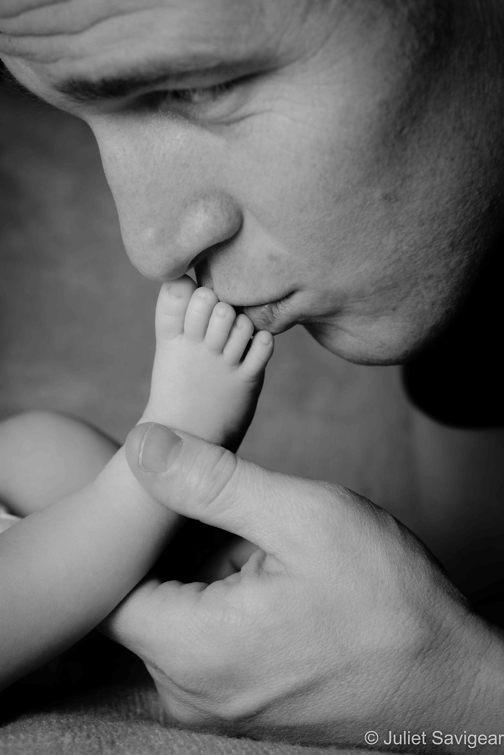 Daddy kissing baby's foot