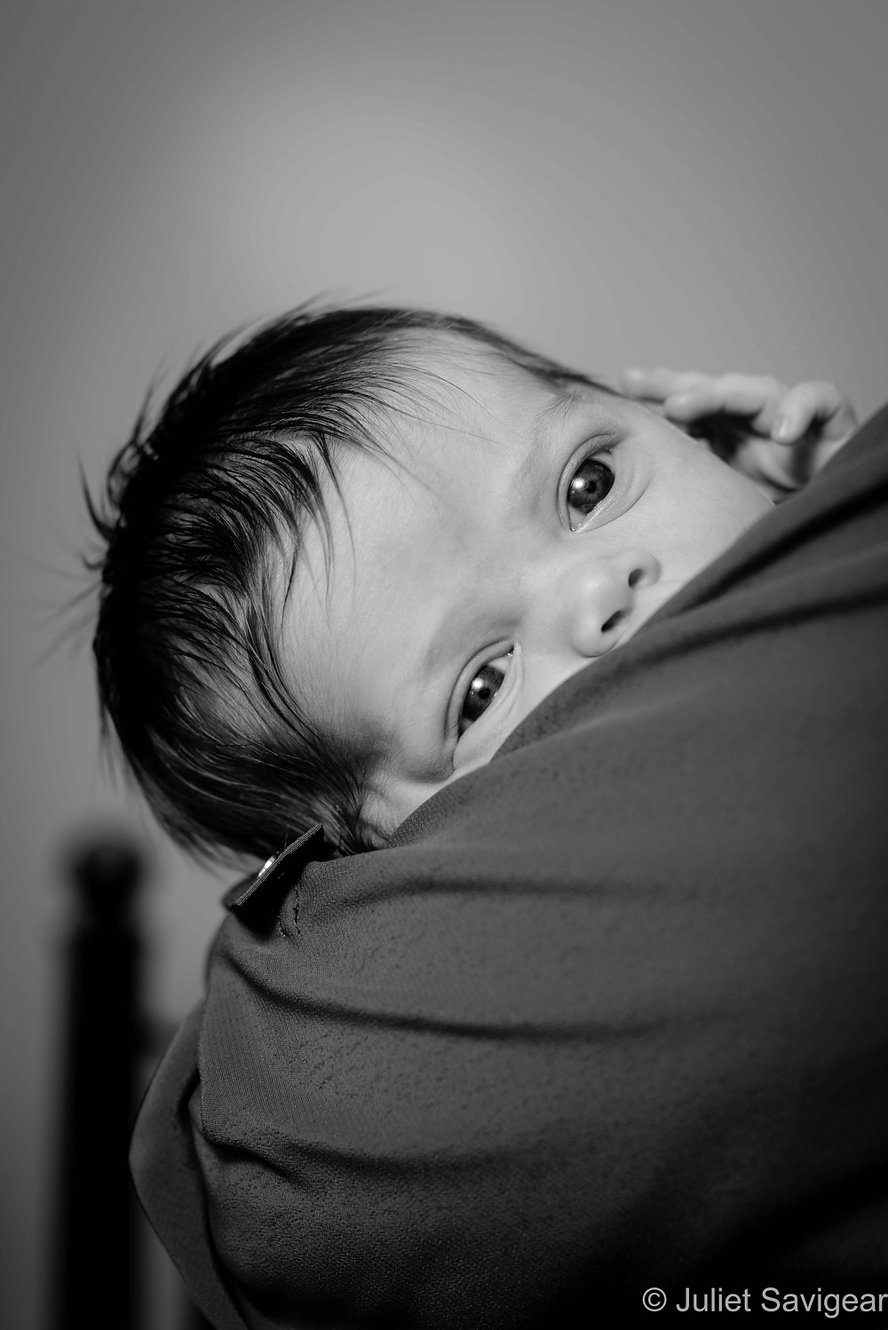Newborn baby peeking around shoulder
