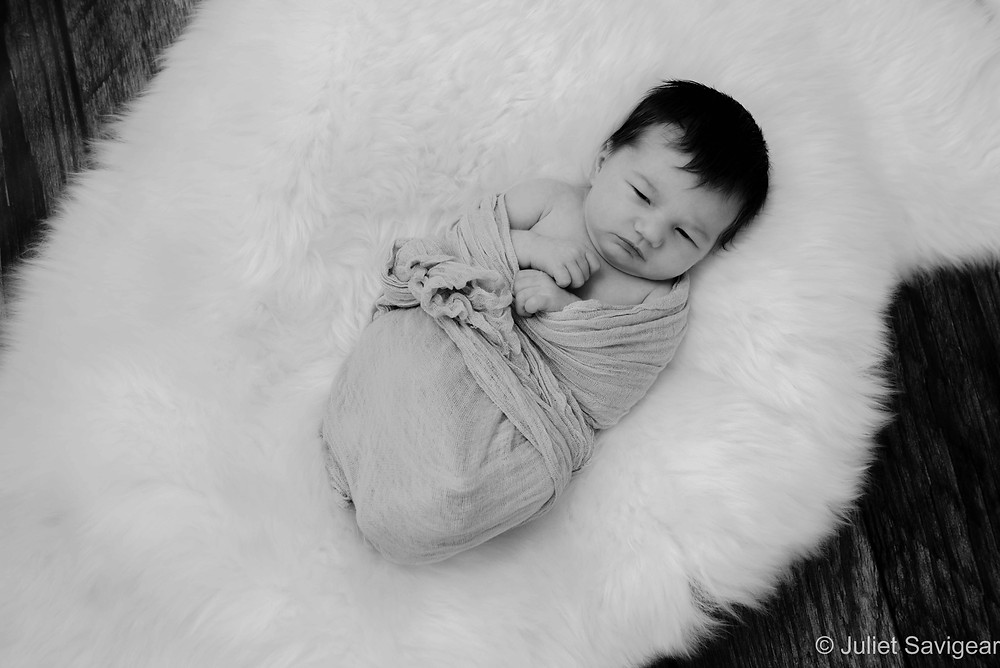 Newborn baby on sheepskin rug