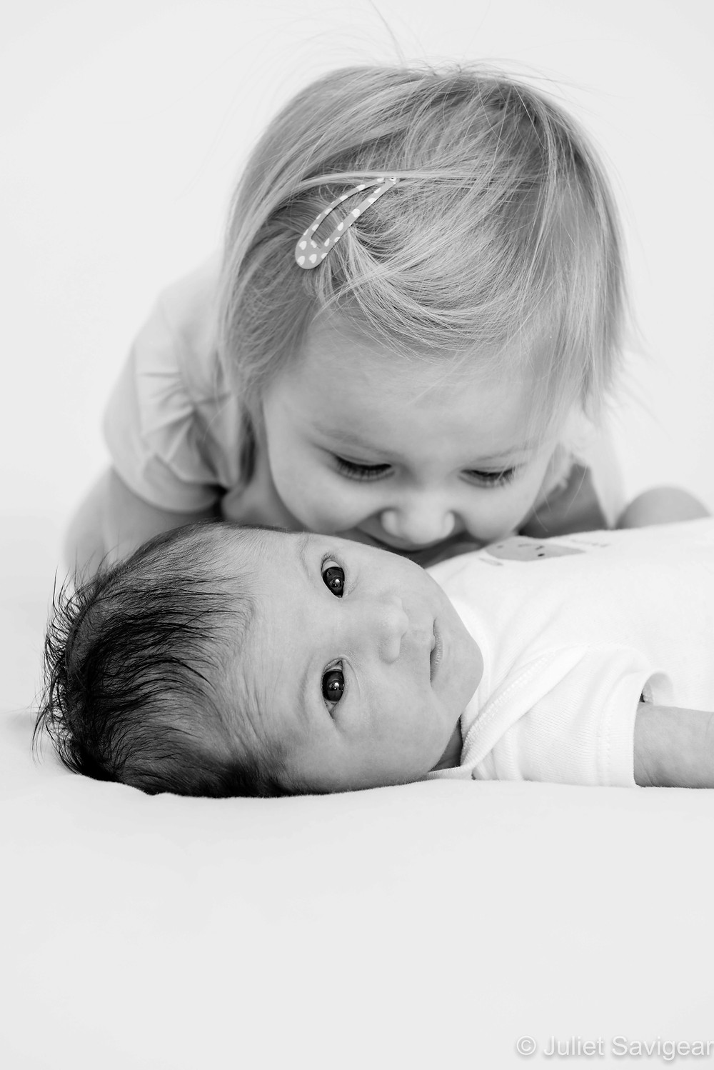 Kissing her new baby sister