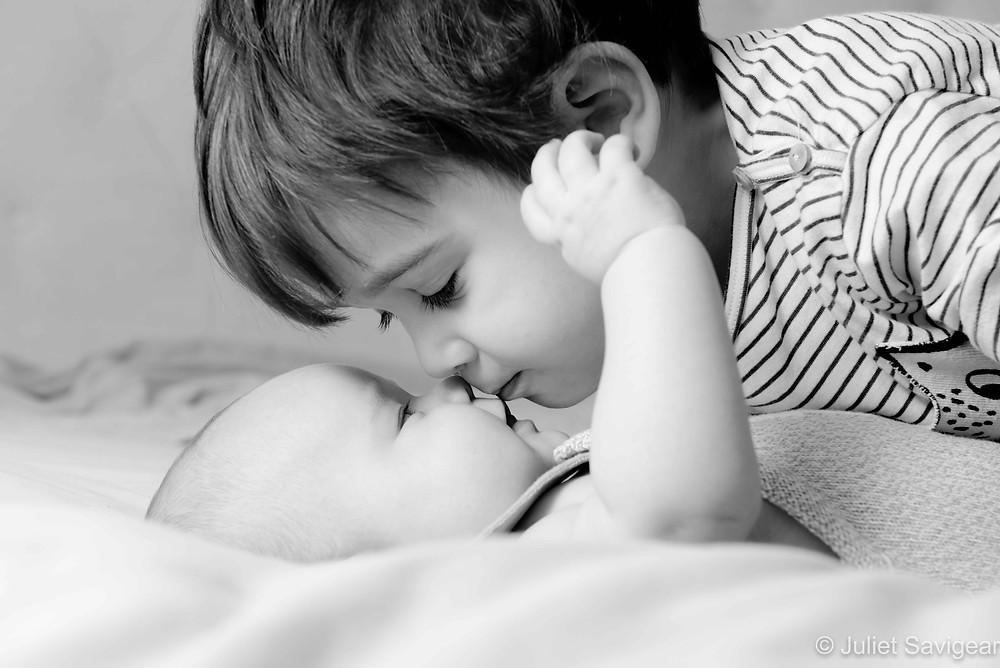 Toddler kissing his baby sister