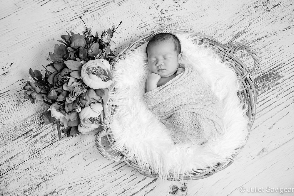 Newborn baby in basket with flowers