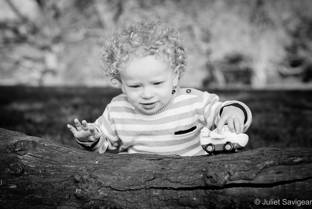 Toddler playing on a log