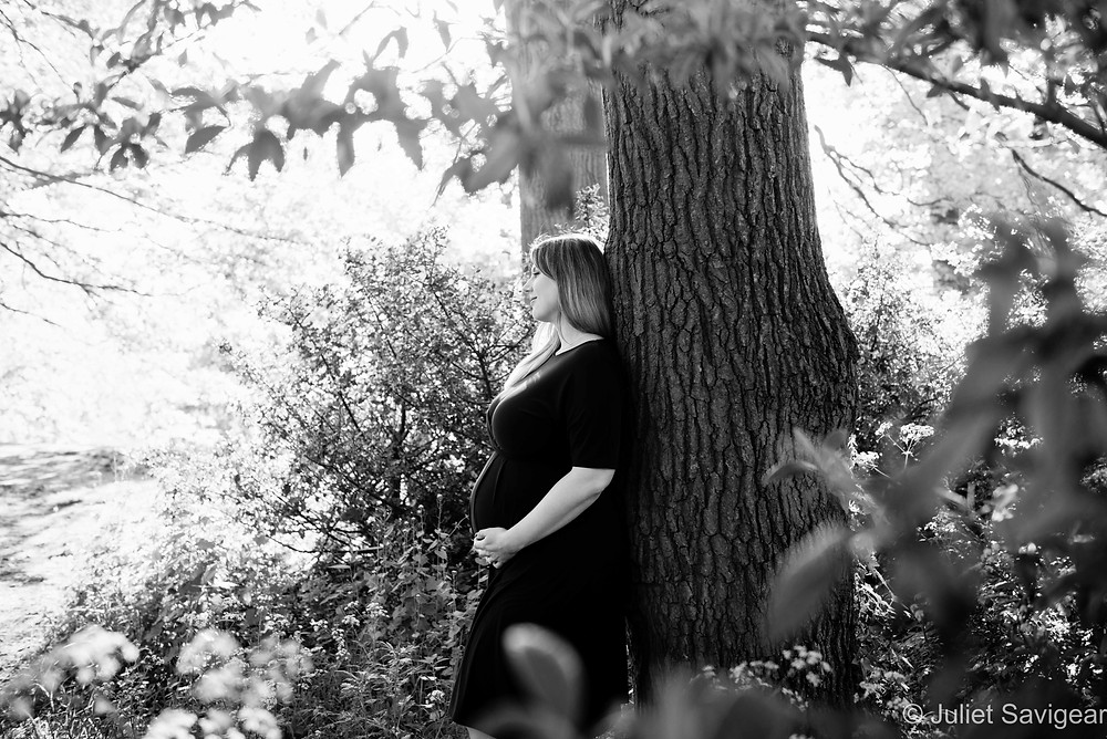 Pregnant lady leaning against a tree