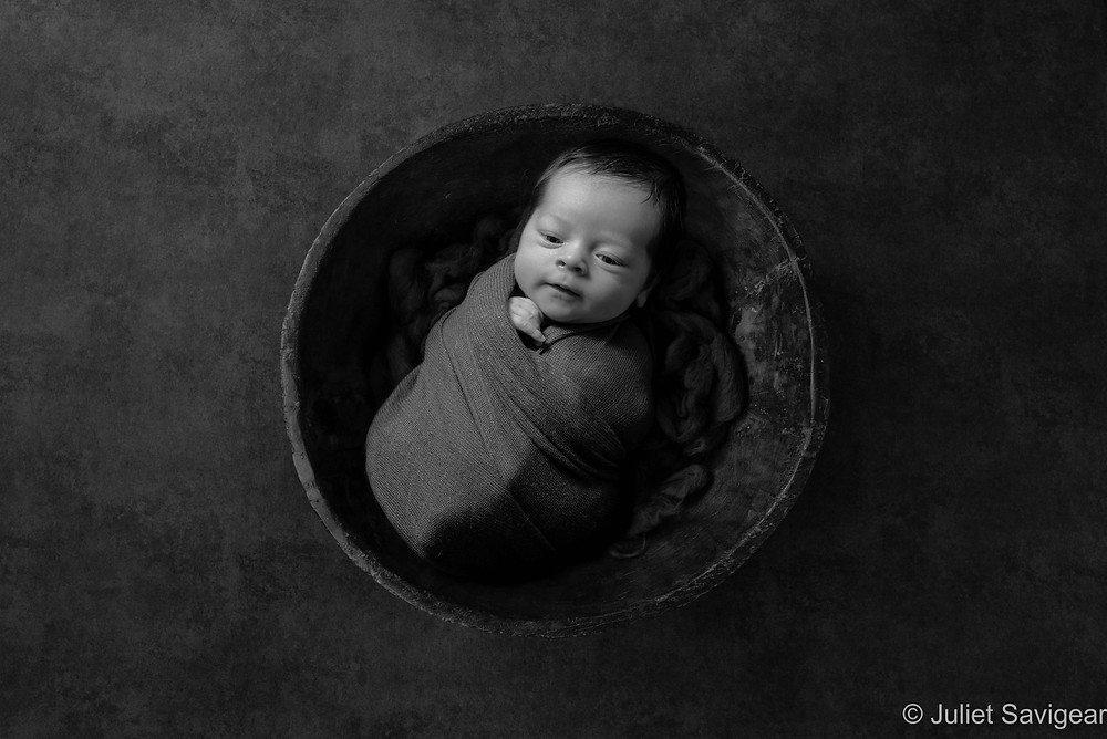 Newborn baby in wooden bowl