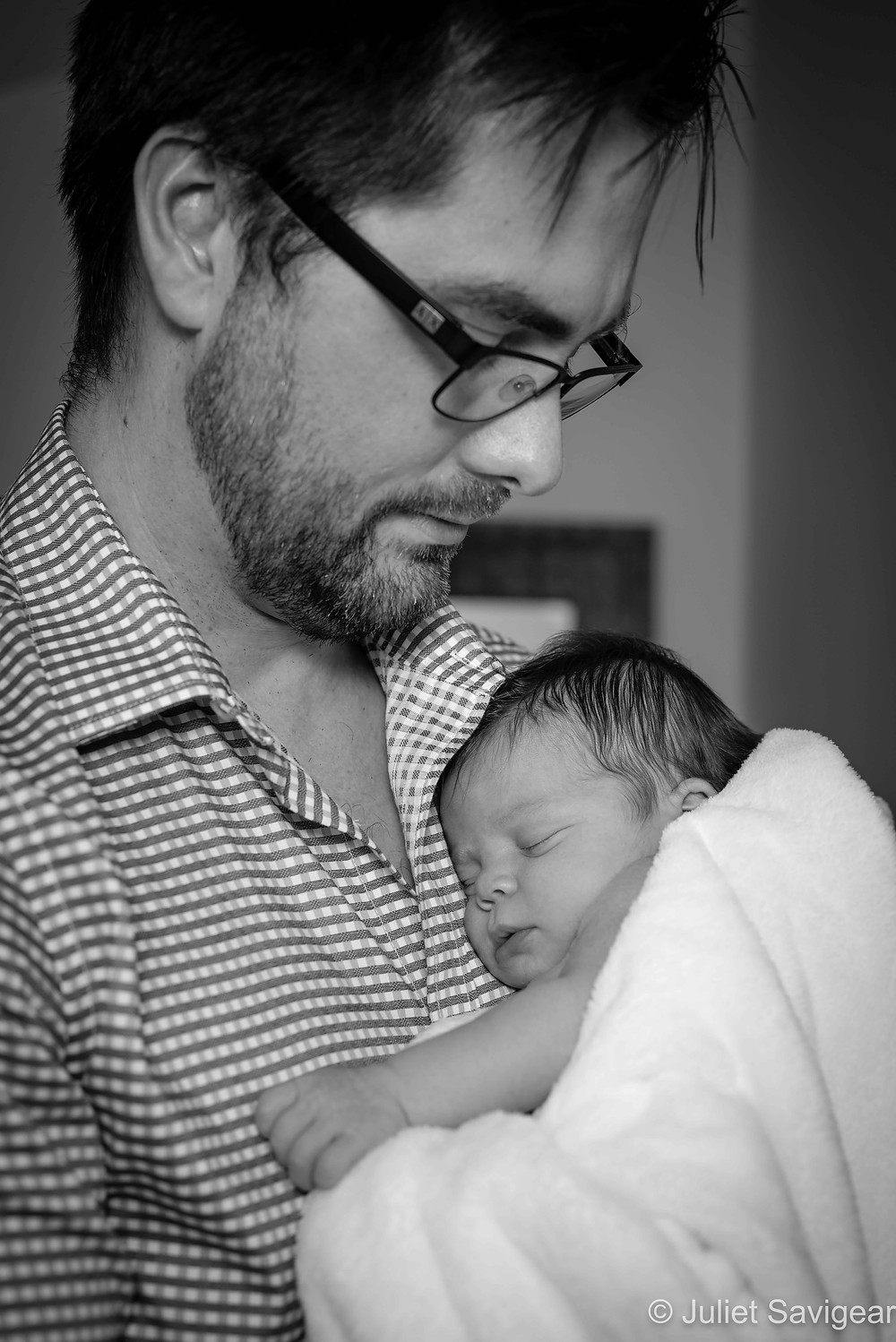 Newborn cuddles in daddy's arms