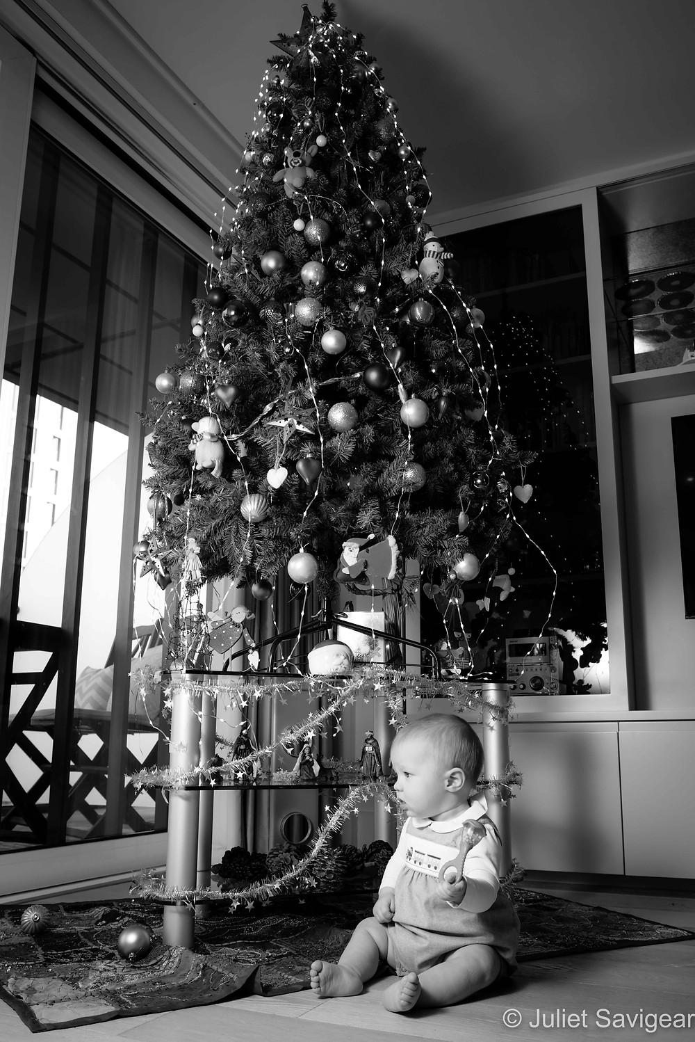 Baby sitting by Christmas tree