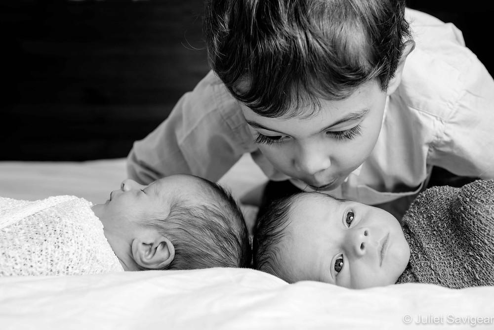 Newborn twins with big brother