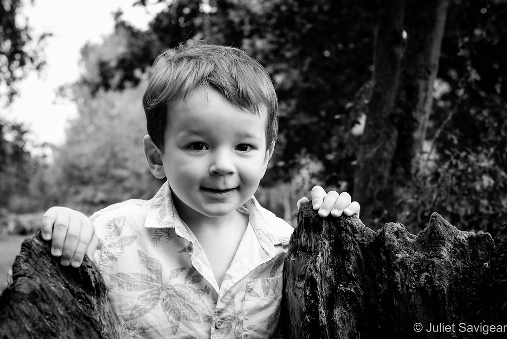 Boy peeking over tree stump