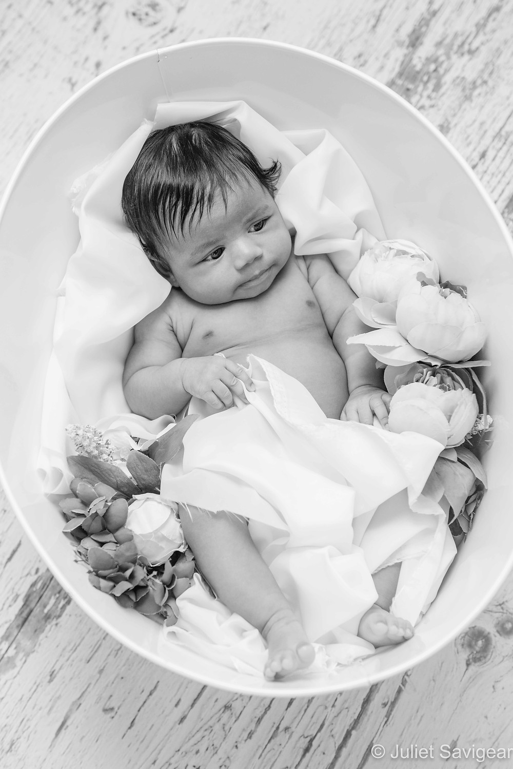 Baby girl in bucket with flowers