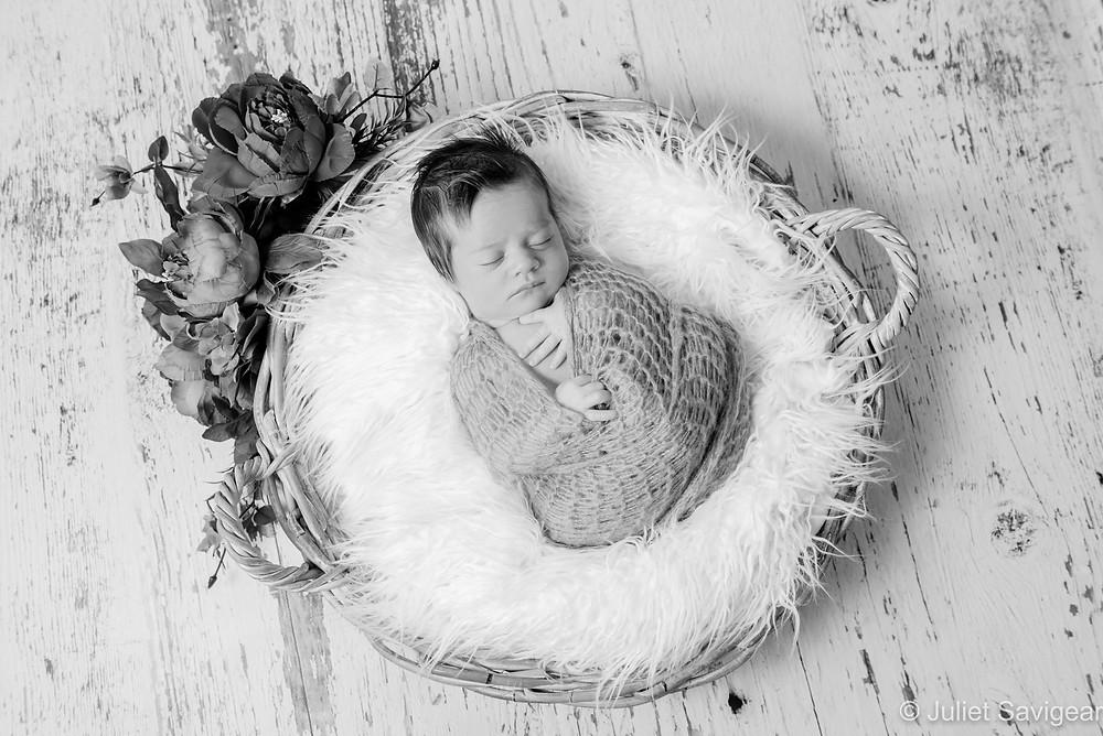 Newborn baby sleeping in basket with flowers