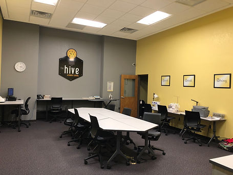 The Hive makerspace has a large table in the center and stations around the room for creating