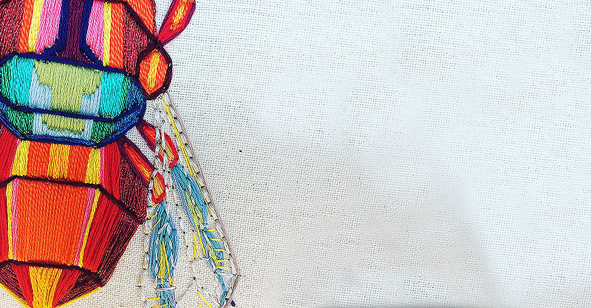 close up of an embroidered bee. The bee is designed in a multicoloured and abstract style.