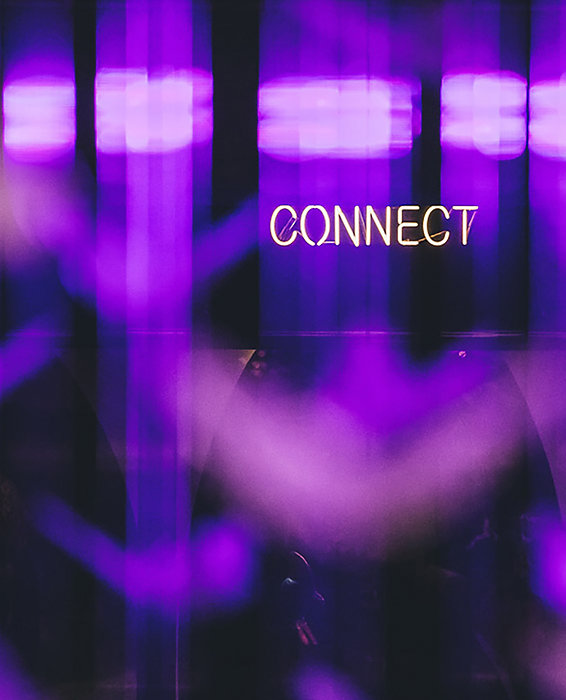 The image shows a reflection of the 'connect' light sign above a display case in living worlds. The photo introduces the talk to us section, click on the button and below to access and communicate with us.