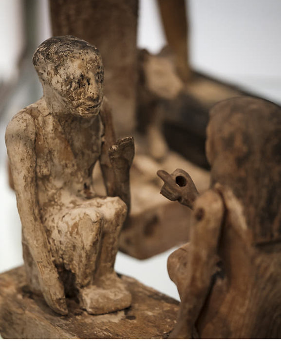 The picture shows a detail of carved wooden statuettes of Egyptian funeral equipment. The two subjects placed frontally in a kneeling position seem to interact with each other. The image introduces the resources for carers section. click on the link below to navigate it.
