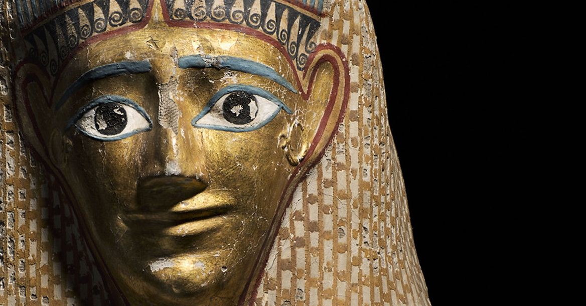 Mummy mask made of linen soaked with wet plaster, which was then moulded, allowed to dry, and painted and gilded. (This material is known as 'cartonnage'). The mask has a gilded face and a tripartite head-dress or wig, painted to represent curls and plaits, with a fringe over the forehead. This suggests that the mask was made for a woman. It shows her in the idealized, almost divine form that the dead hoped to have in the afterlife. At the ends of the head-dress lappets, some of the gods of the dead are depicted, including Osiris.