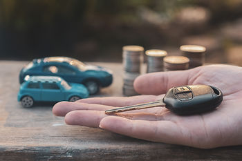 hand-holding-key-of-car-and-model-coins-