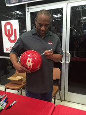 Billy Sims Autographing Oklahoma Sooners Helmet
