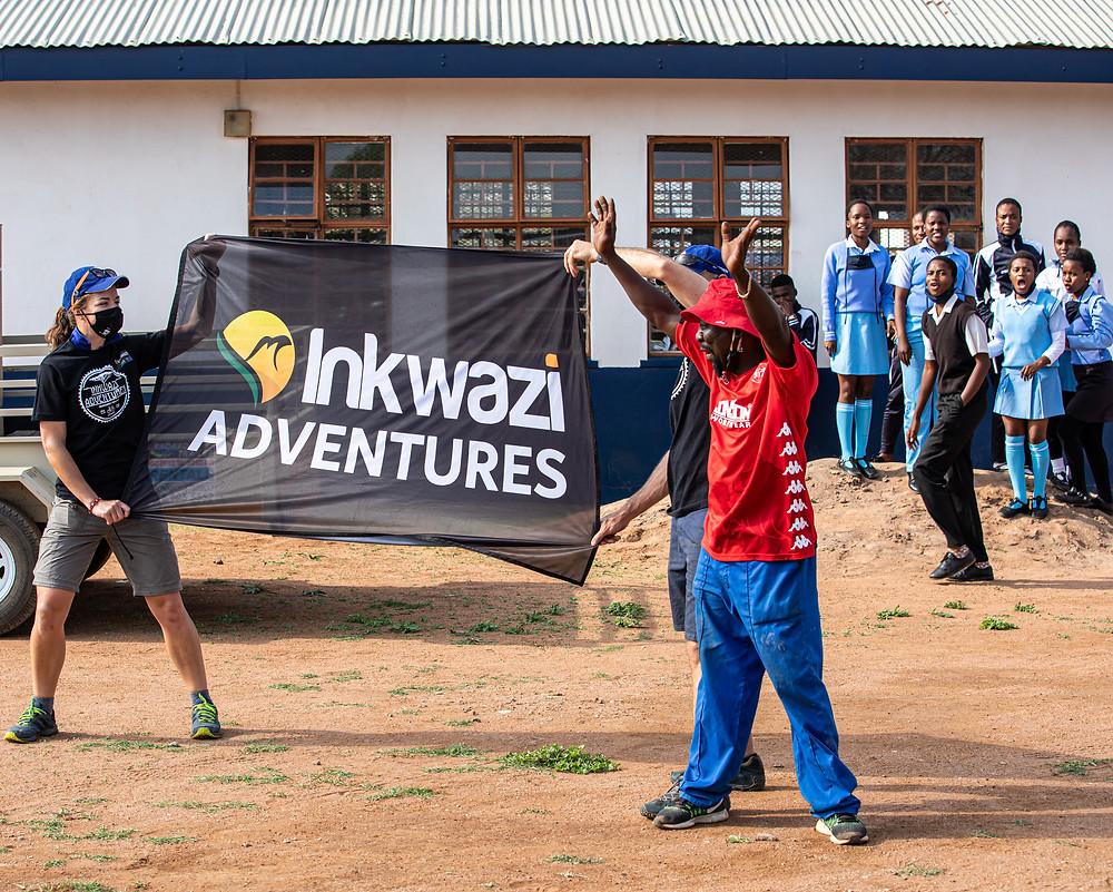 Two people holding Inkwazi Adventures Flag
