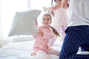 happy-family-having-pillow-fight-in-bed-