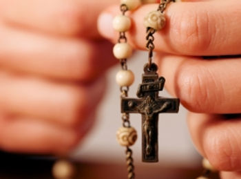 Hands praying with Rosary