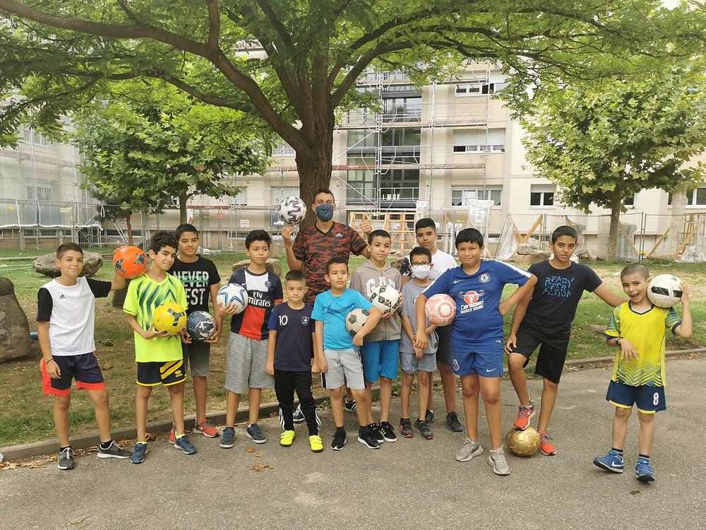 Initiation Football Freestyle à Strasbourg. Le freestyler a donné ses conseils aux enfants pour apprendre les gestes techniques avec le ballon et débuter dans le foot freestyle. Ses démonstrations ont ravi le public du quartier.