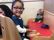 All smiles, Kaylee is wearing big glasses and holding a toy iron at a bench with a red cushion.  A doll sits at the far end of the bench.  Kaylee is sitting in a high-backed chair, looking over her shoulder at the camera.