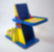 A painted backrest board, about four feet tall, forms a 60 degree angle with its floor base.  The backboard has slightly raised sides and an adjustable attached tray.  Both are brightly painted in blue and yellow, with red highlights.