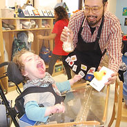 "A young student in a wheelchair with an attached plexiglass tray is laughing as an adult shows him a rubber duck embedded in a 4"" x 6"" white card.  The adult, a man with glasses and a beard, is holding a spray bottle pointed toward the boy and is smiling.  The background shows classroom shelves."