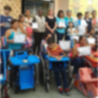 A group of people of various ages pose for a photo. Some are standing and some students are seated in wheelchairs. Many of the  adults in the photo are holding certificates. One student in the photo has a blue cardboard tray attached to his wheelchair. Next to him sits an empty wheelchair with a blue seat insert that fits the chair from the top to the footrests. The insert is painted blue and has a cardboard tray the same color.