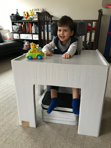 Benny, seated, is leaning on the box-like gray table in front of him, which holds a toy car with an animal passenger.  The cutout between the table legs shows his feet resting on the footplates of his custom chair, and the headrest shows on either side of his head. Behind him is his bed and shelves with books and toys.