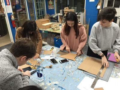 Four teenagers work on cardboard pieces on a workbench holding rulers and utility knives, as well as three cell phones. Behind them is another bench with cardboard projects in process.