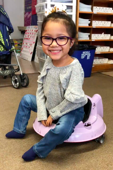 A small girl with glasses is smiling as she poses for a picture. She is seated on a round pink seat with a low back and wheels. The seat itself is low so that her feet can rest on the floor.