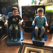 Two young boys sit side by side in the blue cardboard chairs on bases.  In their upright posture, their arms rest comfortably on the armrests with fingers curving over the front edges.  The footrests position their legs so their thighs are parallel to the floor. Though the older boy wears glasses and the younger does not, the family resemblance between the smiling brothers is evident.  In the background are bookshelves and a floor fan.